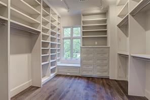 The large walk-in closets in the master are appointed with hardwood flooring, soft track lighting and custom built-in shelving and cabinets.