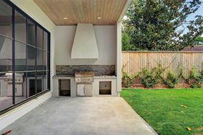 The outdoor kitchen is now further along than in this photo. The stone tile backsplash extends to the ceiling. Note that the tiling covers the patio as well as the upper part of the driveway so that you can have a large outdoor entertaining area. The garage floor has an epoxy finish in a complementary color and double French doors on the side that can be opened to the yard, creating additional covered space for entertaining guests. There is also wiring in the patio ceiling for speakers.