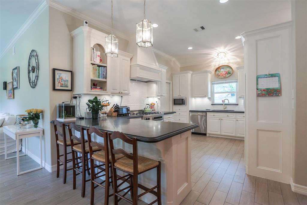 Large renovated kitchen includes a 4 stool breakfast bar, granite counter-tops, and twin pendant lights.