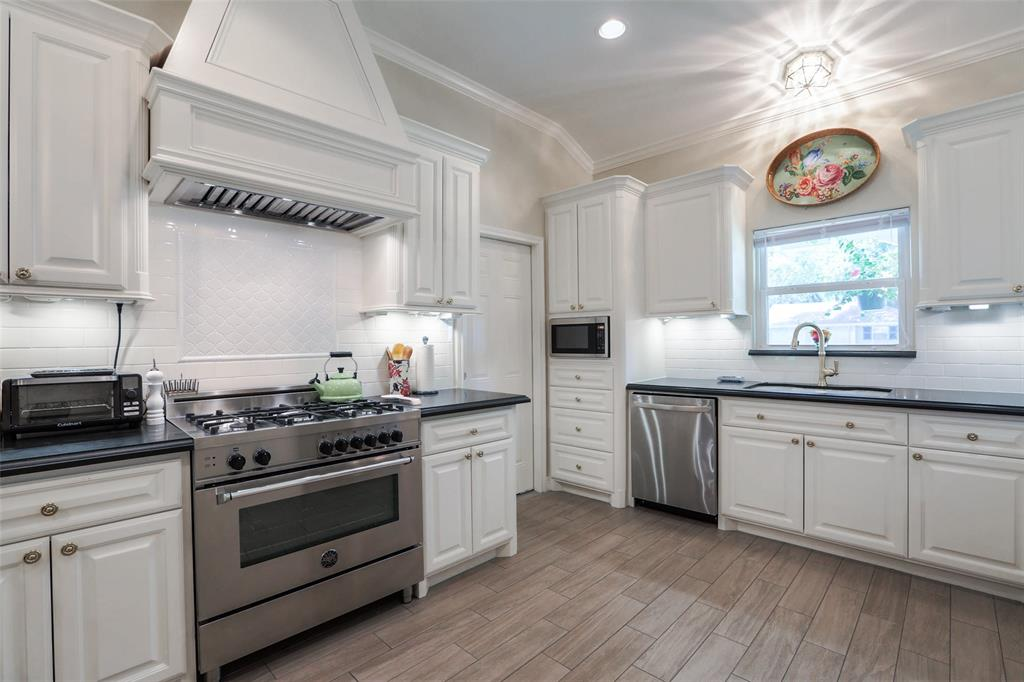 This kitchen includes a Bertazzoni pro-style Range, built-in Microwave, and pro-style venthood surrounded by custom millwork.