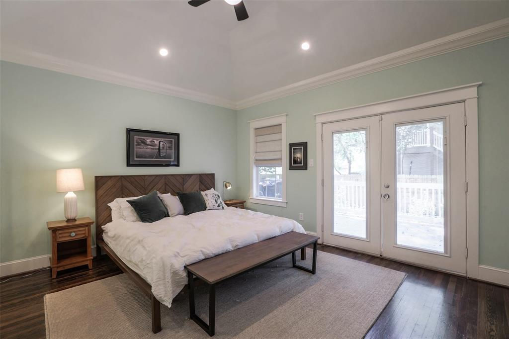 The large master bedroom offers vaulted ceilings, recessed lighting, wood floors, and direct access to the back porch.