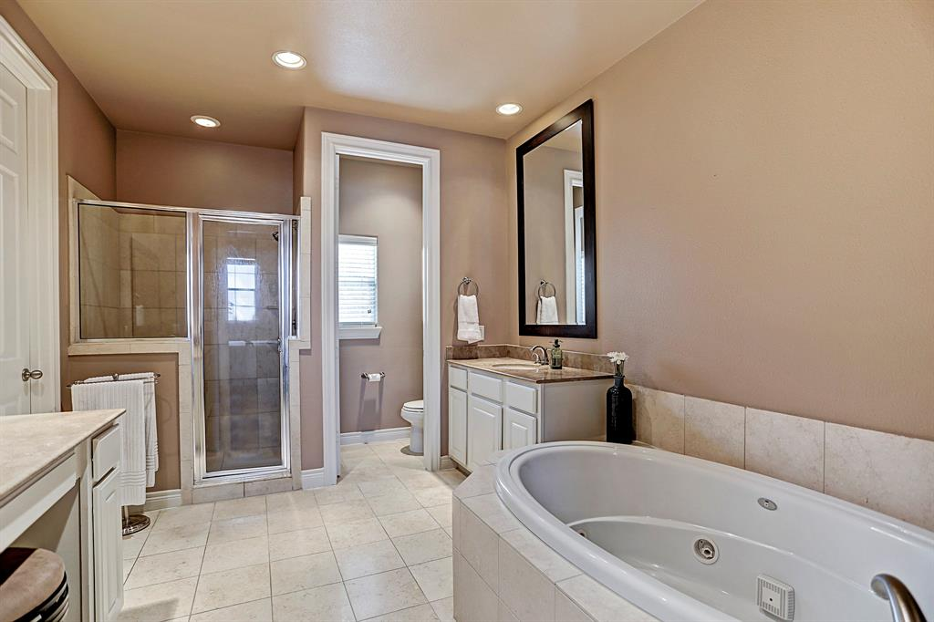 Relax in style in this jacuzzi bath. This Master bath has dual vanities and a separate shower unit.