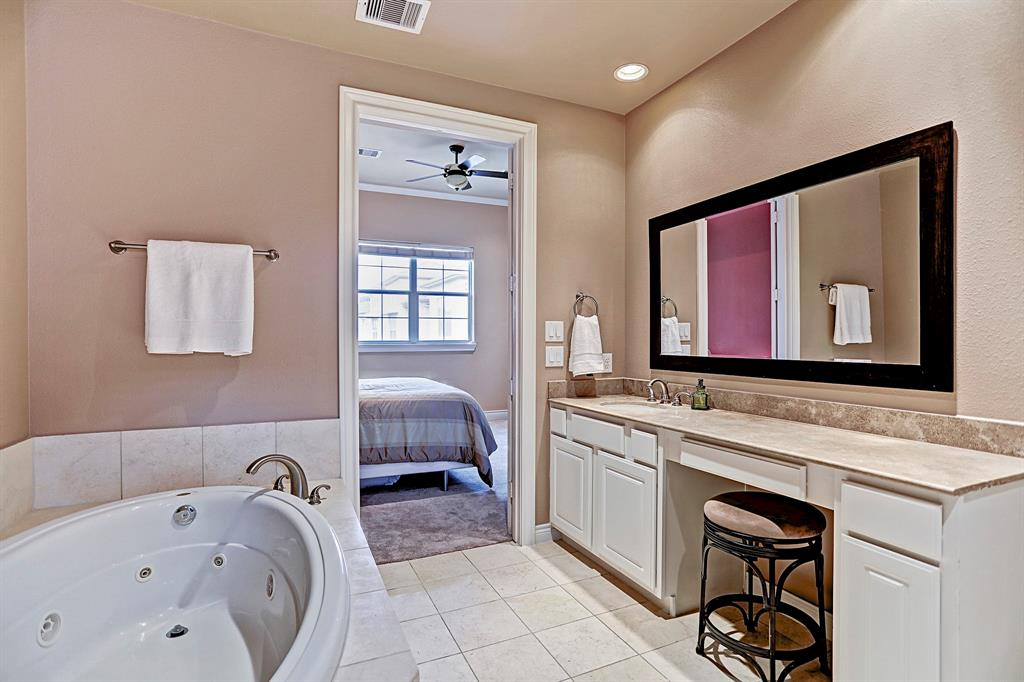 Light and airy feel to this master suite. Large vanity space for accessories, and a sit down makeup area.