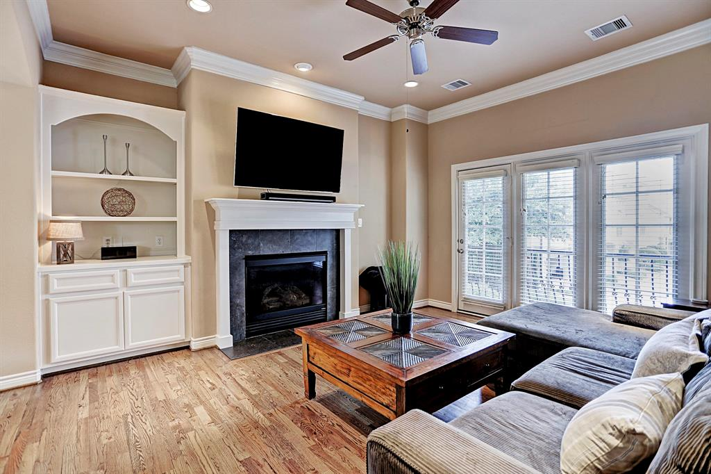 Bright and open living area with grand fireplace, built-ins and wooden floors throughout.