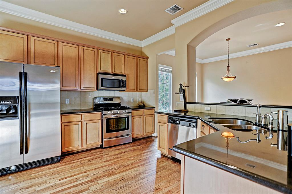 The stainless steel appliances, open bar areas, and vast storage space make this kitchen ideal.