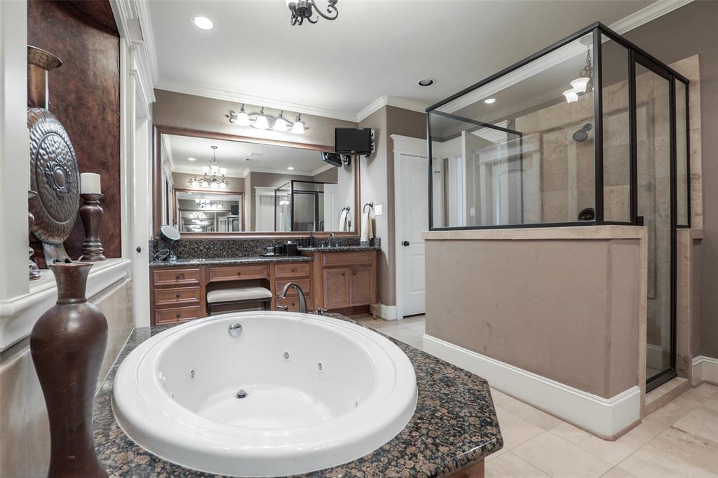 Master bath features dual vanities, large shower and jetted tub.