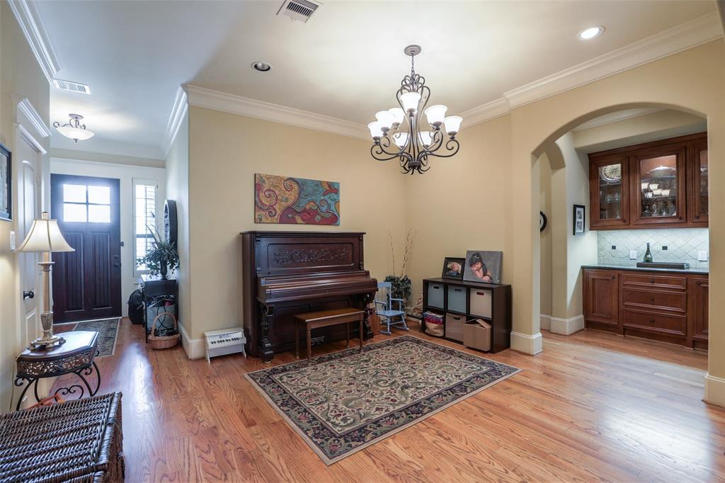 Dining space that opens to the living room features wood floors and crown molding.