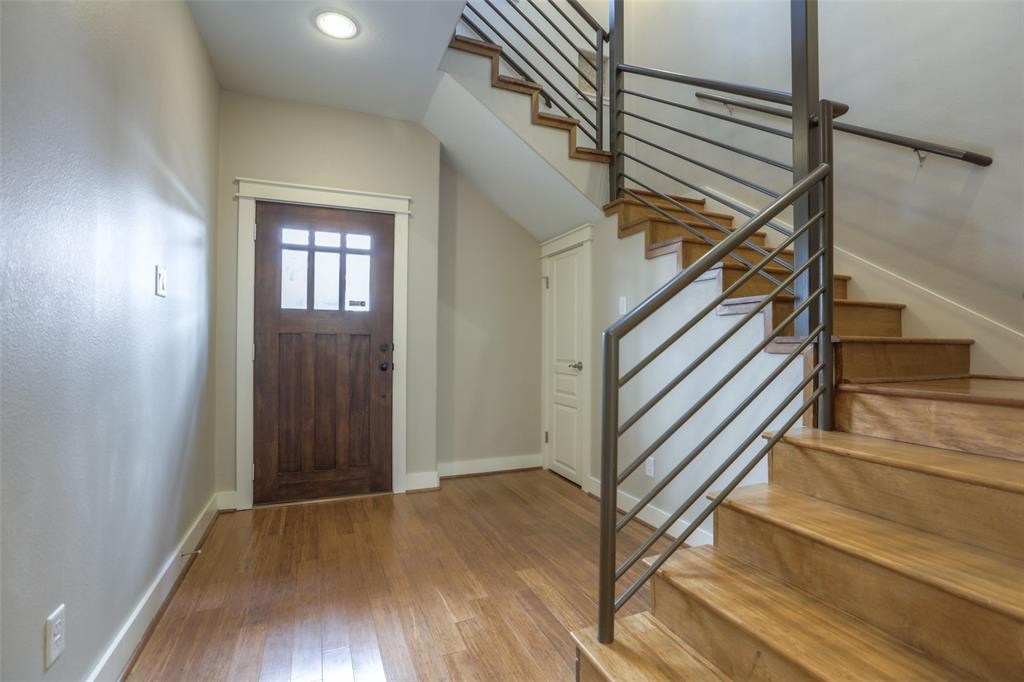 Entry way with storage closet under the stairs and modern design railing.