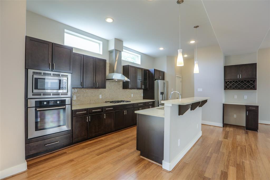 Modern kitchen features quartz counter tops, stainless steel appliances and lots of storage