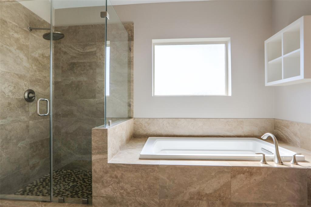 Master bath features large shower with separate tub