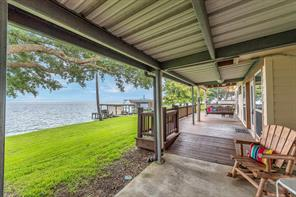 Relax after dinner on your covered deck with a cool beverage and enjoy the soothing sounds of the water lapping at the bulkhead.  Your Boat House and Slip can be seen in the background.