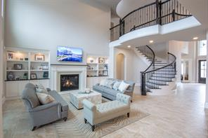 Let's proceed on into the home and take a look at the family room. Notice the two story ceiling and the dramatic wrought iron stairway and balcony. Built-in cabinets anchor the gas fireplace. This room is just lovely and quite impressive. It is a perfect balance of beautify and comfort.