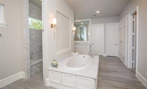 The spa-like master bath is a true scene stealer. Beautiful wood floors, marble and lovely finish work provide a very Zen vibe to the space. It truly is so well-thought out. There are two vanities separated by a walk-through two-person shower. There are also separate water closets.