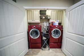Double doors swing open to reveal the washer and dryer.