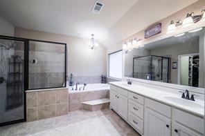 The master bath offers a separate shower and step-up whirlpool bath. The vanity is spacious with dual sinks.