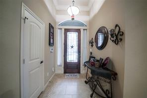 Greet your guests in this entrance which features an inlaid glass door and high ceilings with crown molding.
