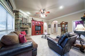 The living room offers a floor to ceiling fireplace, large windows, recessed lights, crown molding and a ceiling fan.