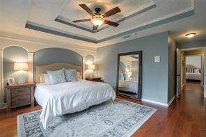 HUGE master bedroom boasts a new ceiling fan, double recessed ceiling and decorative archway trim. Loads of character! Wood floors throughout the house. Across the hallway, a view of the guest bedroom.