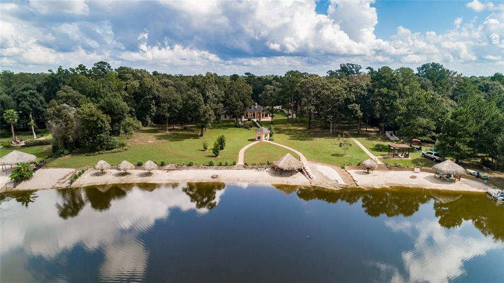 Lakefront Beach!  One of a kind, this rare find has its own private sandy beach on a serene lake.  Expansive lake front property sits on 2.48 acres, offers one story living at its best.    Spectacular sunsets!  One large beach cabana, three palapas and a fire pit provide the perfect atmosphere for your entertainment.   Many custom features throughout include, crown molding, high ceilings and built-ins.  Split plan has formal living, dining and large study. Huge master suite with built-ins garden tub and separate shower. Gourmet Kitchen is open to living area with granite, stainless, butlers pantry, bar and built-in desk.  Enjoy resort living at home on the lake!