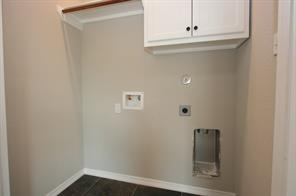 Utility room has extra storage cabinets up above where the washer/dryer go as well as a drying pole.