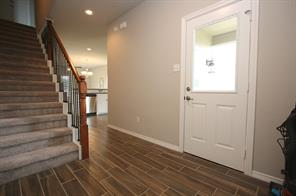 Entryway once inside the home has nicer tile flooring that replicates hardwood. Wrought iron rails and stained posts on the staircase dress up the home as well.