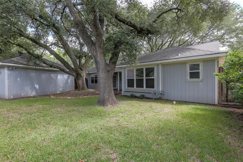 Fully fenced back yard with mature oak trees and covered patio