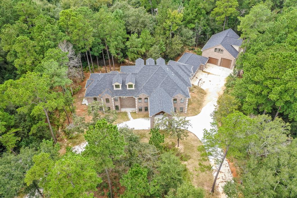 Gorgeous estate on 8+ acres. Secluded, wooded location, next to lake in gated community! Appraised at $1.7M when finished, this 3-story home is ready for your selections, flrs, cabinets, etc. Pre-wired & plumbed for state of art features, such as 11.2 ATMOS XD Movie Theater with own vent sys, CAT 6 data cables in all BRs, office, library, etc. 3-story elevator shaft. Whole-house stereo/intercom, camera, central vacuum & water softener. 20' entry & 10' mahogany doors. Secluded master BR located in private wing, 75 ft from any other BR. Huge master bath contains massive closet with laundry shoot, bidet, Italian marble shower with his/her heads, wand, rain head in vaulted ceiling. Has an office & separate library, 3 living rooms, 2 kitchens, both formals, huge game room, big BRs with private baths & large walk-in closets. Balcony & porch with outdoor kitchen. 10' ceilings 1st. MIL suite with private entrance. Large barn with 2 BR full suite. Contact realtor for complete list of features.
