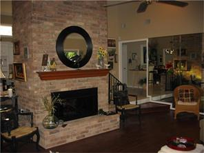 Living room with large fireplace as room divider and great focal point for entertaining guests.