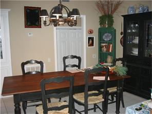 Well lit Dining room with tiled flooring.