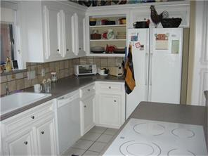 Kitchen view of beautiful cabinetry,flat surface stove top, built in shelves, and more!