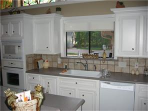 Large Kitchen recently remodeled with new countertops and appliances. Notice the unique stained glass windows in top left corner that bring natural light to this beautiful home.