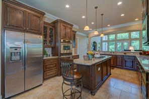 The Kitchen features pendant lighting, ss appliances, double ovens, custom cabinetry, granite counters, and a Kitchen Island with gas cooktop.