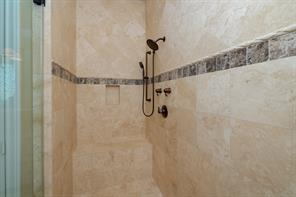 Travertine tile from shower floor to 10' ceiling!  There's even a seat in this shower!