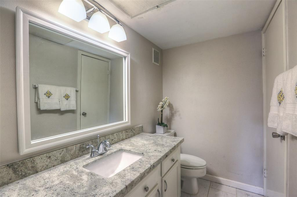 Hall bathroom with granite counter top and updated tile.