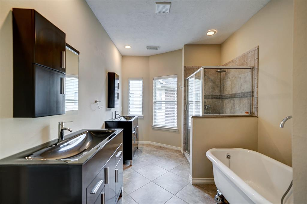 The master bathroom includes double contemporary vanities, a claw foot tub, and a separate stand up shower.