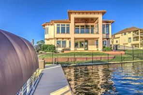 View of the back of this beautiful Mediterranean style home. Pavers lead from the back tiled steps to the boat dock. Look at all of those beautiful windows.!!!
