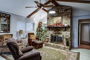 Brick wood-burning fireplace with mantel, living area with brick-laid pattern in the tile. Retro light fixtures.