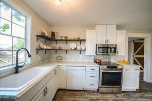 9651 offers a bright and airy country kitchen with large deep sink and open shelves and cabinets.