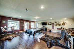 Upstairs game room offers an abundance of natural light, wood floors and a balcony overlooking the pool and lake.