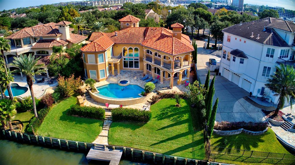 WATERFRONT ESTATE:  Enjoy the best views of Clear Lake in this 5/5.1 Tuscan beauty and experience the unique Lifestyle of Waterfront Living.  Featuring 2+ levels of architectural excellence with upscale appointments, high ceilings,soaring windows, art niches, stone columns, arched openings & imported doors & cast stone FP's. Exquisite stone flooring & elegant mahogany cabinets. Open concept w/chef's kitchen boasting a huge island w/ veg.sink & designer SS appliances. Two dining areas, large breakfast bar (seats10) & walk-up wet bar & wine grotto. Two huge masters w/ sitting areas, multiple living areas & state of the art theatre system (ask about furniture).  Summer kitchen w/EGG smoker, SS grill, bar w/sink and an o/s full bath just steps away & more! Fabulous negative edge pool/spa on mobile app. Outside fireplace with Xtra seating make this retreat perfect for year round entertaining. Private pier for a 40' yacht (boathouse ok). Enjoy your private retreat at this signature address.