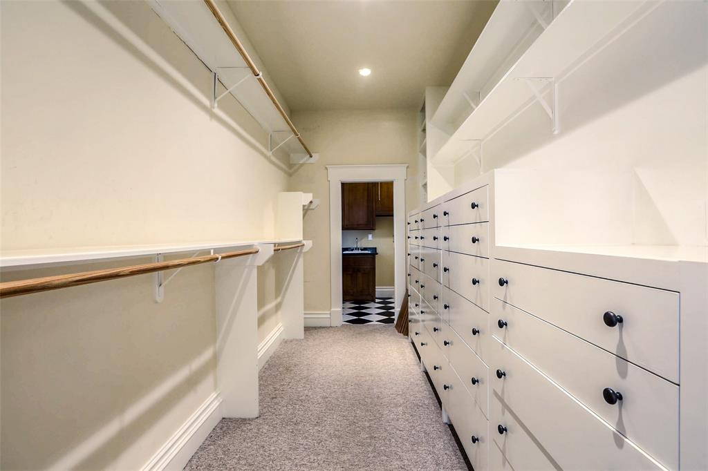 Large walk-in closet with built-in storage and adjacent utility room.