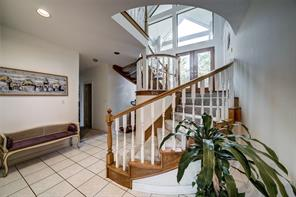 Staircase of the home with the front doors in the background. Home is a split level plan with the living, kitchen, dining and master bedroom up, and two bedrooms plus study and second living area down.