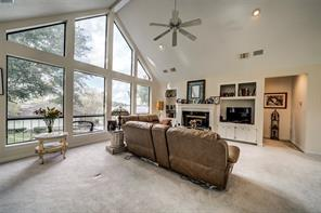 Open living room with vaulted ceilings and lots of picture windows to enjoy the views look across Lake Conroe from.