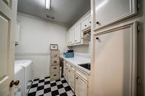 Utility room has lots of extra cabinets and a pre-wash sink..