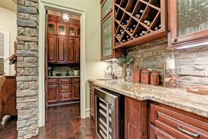 The wet bar adjacent to the dining room, boasts rock backsplash, mini fridge, convenient wine storage and granite counter tops.