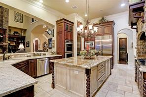 A massive granite island serves as the centerpiece of the kitchen that features top-of-the-line stainless steel appliances, incredible storage capabilities, huge pantry and many custom built-ins.