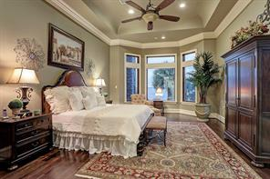Swathed in decorator-friendly paint, the master bedroom boasts motorized shades, bay window, hardwood floors and tray ceiling.