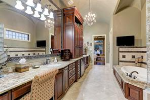 The opulent master bath is engulfed in rich mahogany cabinetry, granite dual vanities, expansive mirror and make-up station.