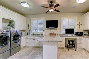 Fantastic oversized utility room doubles as a hobby room.  It features plantation shutters, granite working island and lots of drawers and shelves for storage.
