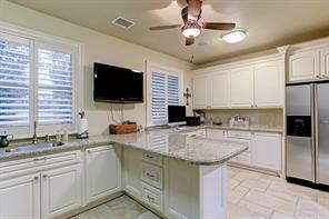 Large sun-lit utility room features refrigerator/freezer and large working area for home projects.